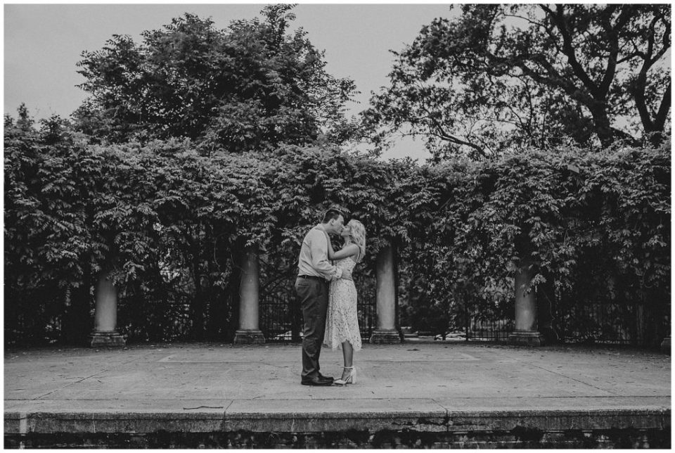 A photograph in black and white of a couple standing at a distance in a veranda lined with old columns and trees as they romantically kiss to celebrate their engagement at Schiller Park in downtown Columbus