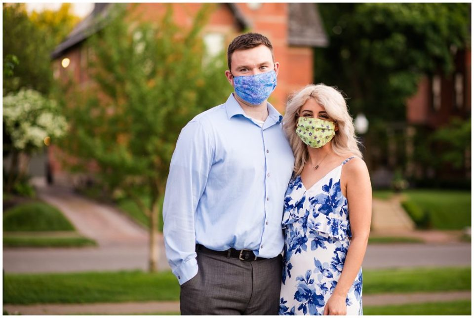 A photograph of an engaged couple standing close together with their COVID-19 masks on, marking the historic time of their engagement during the pandemic at Schiller Park to the east of the brewery District in Columbus Ohio