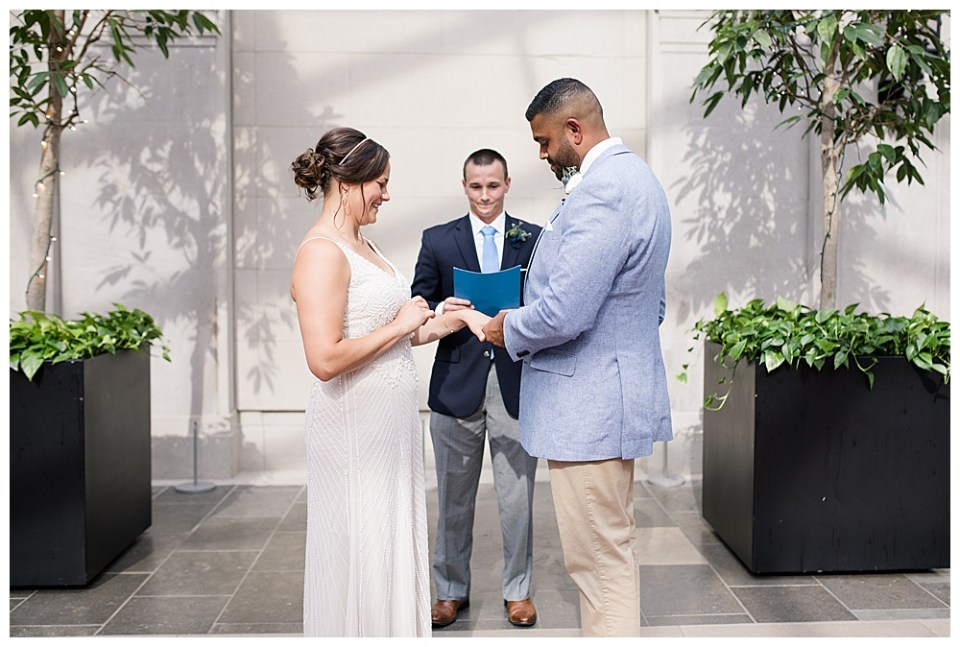 A photograph of the groom placing the wedding ring on his bride's finger as they stand with the preacher at their wedding ceremony, flanked by potted trees with tiny lights at the Columbus Museum of Art in downtown Columbus