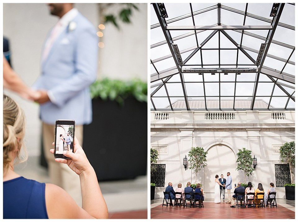 An image of a wedding guest holding up a phone camera clearly focused on the bride and groom, ready to take the picture, as the wedding ceremony proceeds in the background in a Columbus Museum of Art wedding