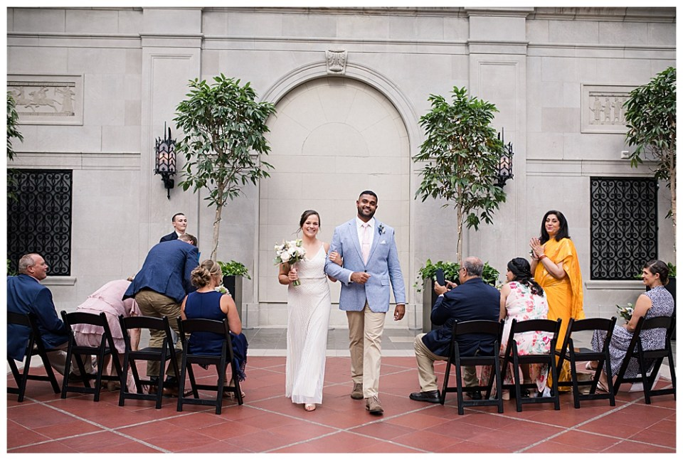 A picture of a bride and groom walking arm in arm down the aisle after their wedding as the guests look on surrounded by a beautiful museum setting with potted trees and a stone arch at the Columbus Museum of Art in downtown Columbus