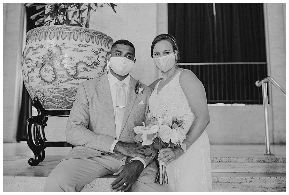A picture of a bride and groom in their COVID-19 masks as they sit together at their wedding venue during the pandemic in a Columbus Museum of Art wedding