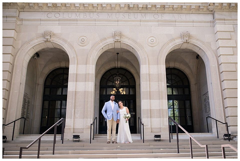 An image of a bridal couple standing outdoors on a stone stairway leading to a dramatic arched entrance to their wedding venue by Alayna Parker - Columbus wedding photographer