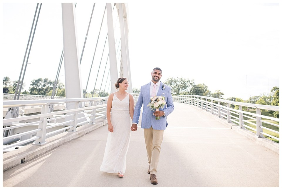 A photograph of a bride and groom walking hand in hand across a bridge as the groom holds the bouquet and they enjoy the afternoon sunshine in a Columbus Museum of Art wedding