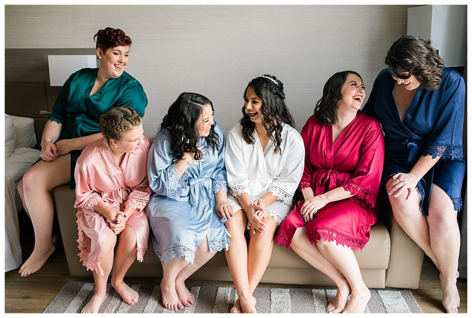A picture of the bride and her bridesmaids relaxed and laughing together on a couch, dressed in their short satin robes before getting ready for the wedding ceremony by Alayna Parker Photography a Columbus Ohio wedding photographer