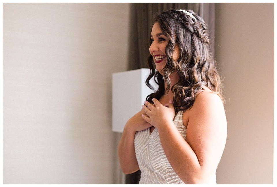A picture of the bride standing dressed in her wedding clothes and makeup, smiling happily with her hands touching her chest in excitement