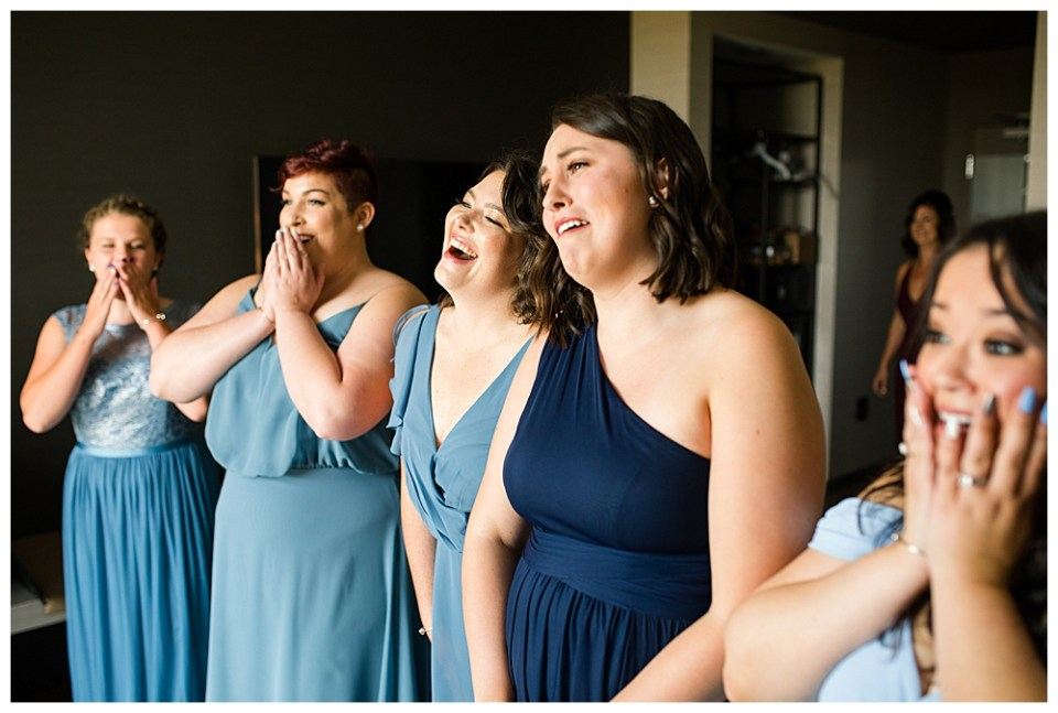 A photograph of the bridesmaids reacting with excitement at their first look at the bride in her dress as they are wearing their beautiful blue dresses