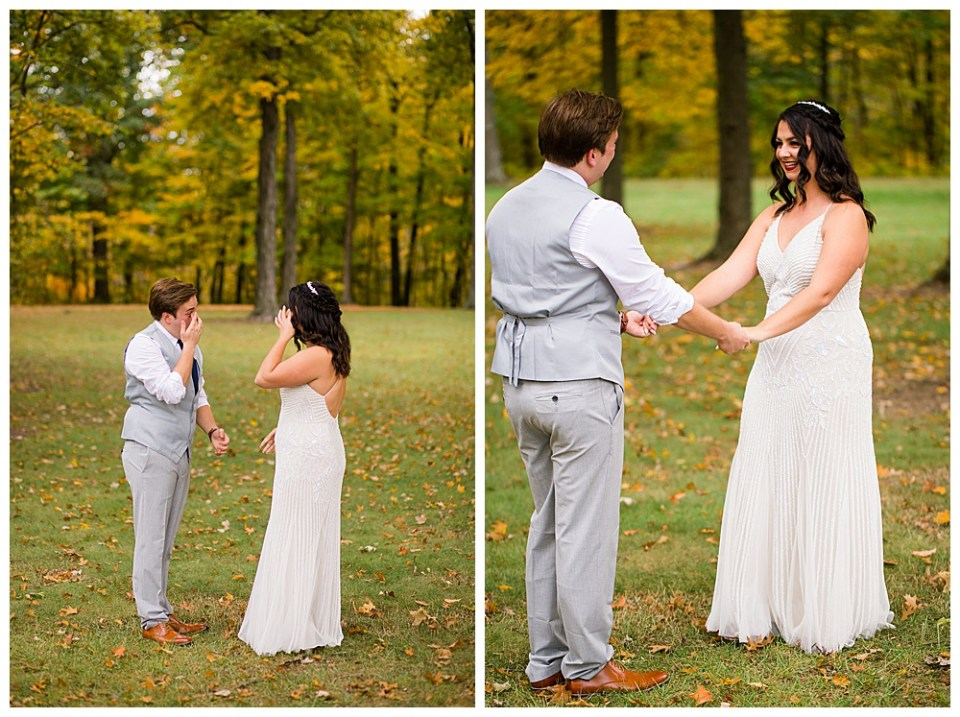 A picture of the groom with his first look at his bride as they hold hands, standing outdoors with a beautiful park setting behind them