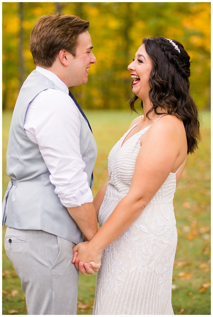 A photograph of the bride and groom standing close, holding hands at their first look, gazing with joy at each other as they anticipate their marriage ceremony