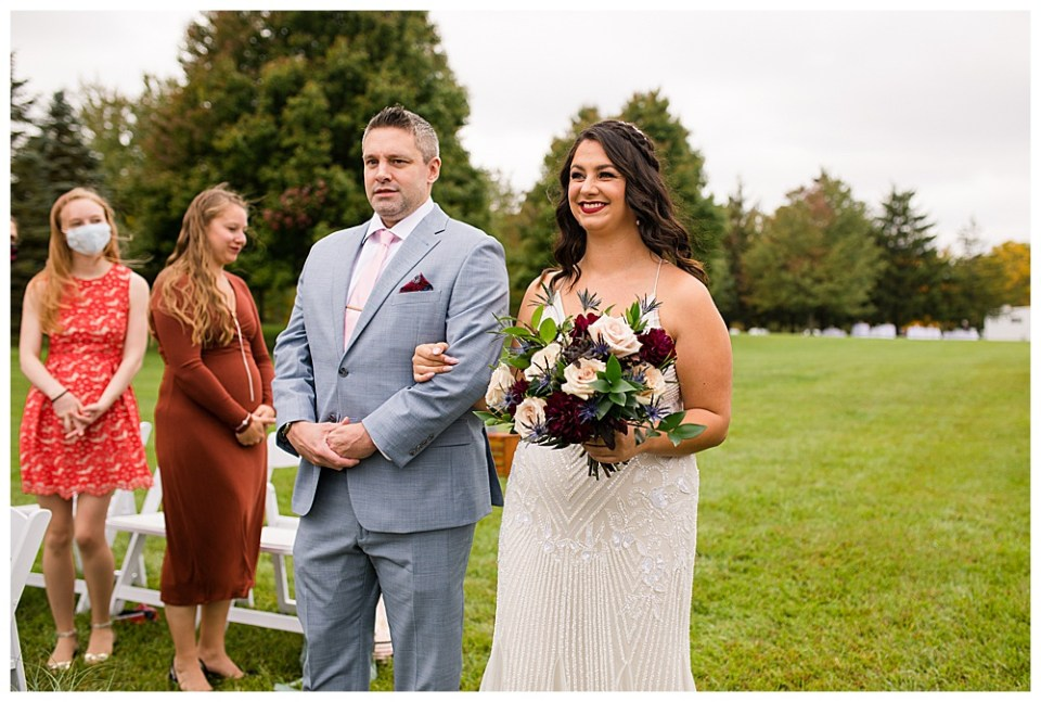 A picture of the bride walking down the aisle holding her father's arm as they hold the wedding ceremony outdoors with guests looking on