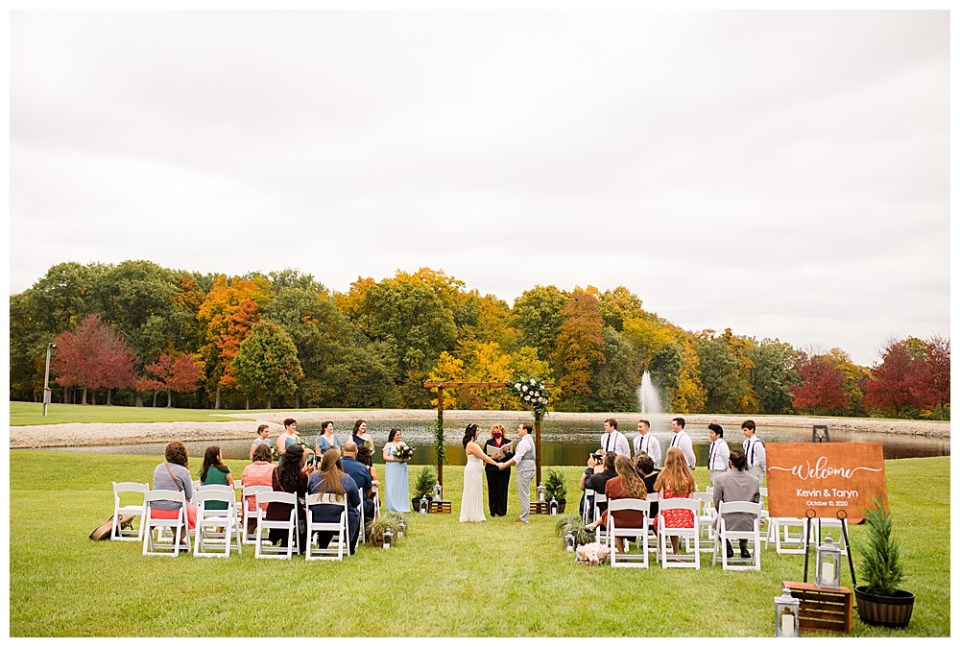 An image from a distance of the bride and groom standing at their wedding ceremony with their officiant and wedding party while guests sit nearby in front of a pond and beautiful fall trees