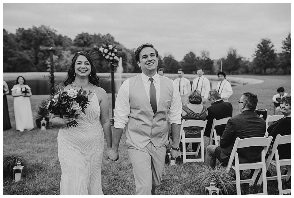 A picture in black and white of the bridal couple happily holding hands as they walk down the aisle at the end of their outdoor marriage ceremony as the wedding party and guests watch behind them
