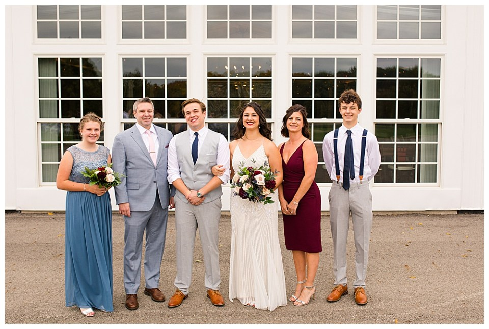 An image of the bride and groom standing with the bride's family, smiling together as they stand in front of a picturesque row of windows outside their reception hall