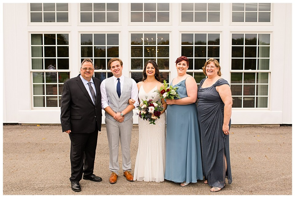A photograph of the bridal couple standing with the groom's family as they smile together outside of their wedding reception venue