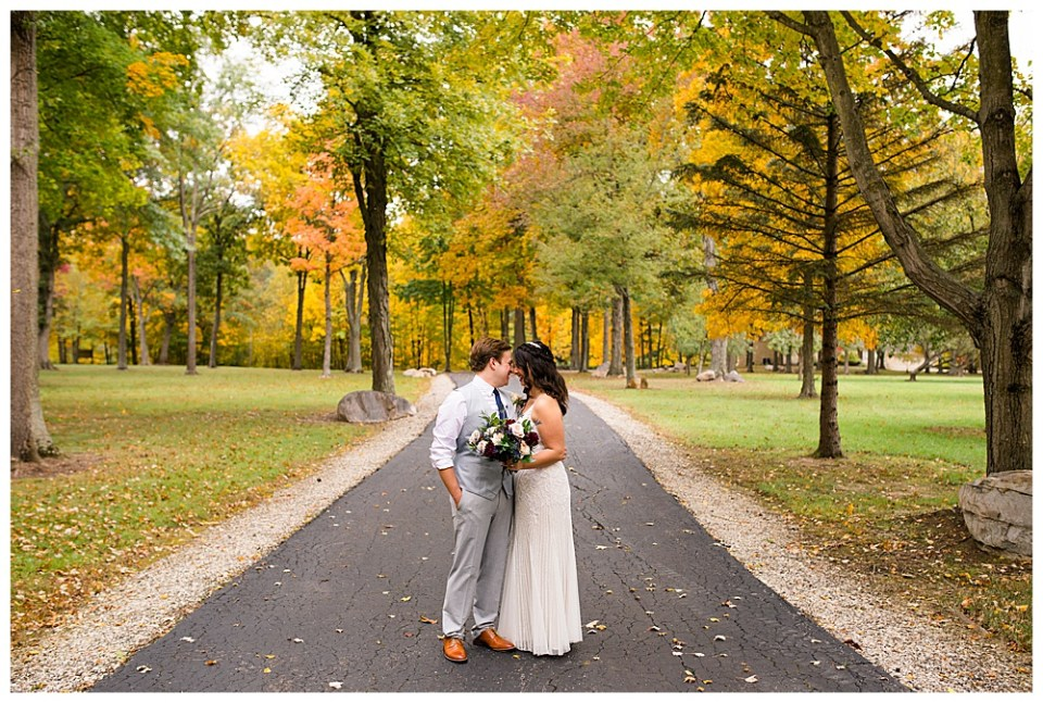An image of the bride and groom standing close together on a quiet road, almost kissing, as they are surrounded by a lovely, spacious park setting of grass and fall trees at Dorral Farm in Marysville, OH