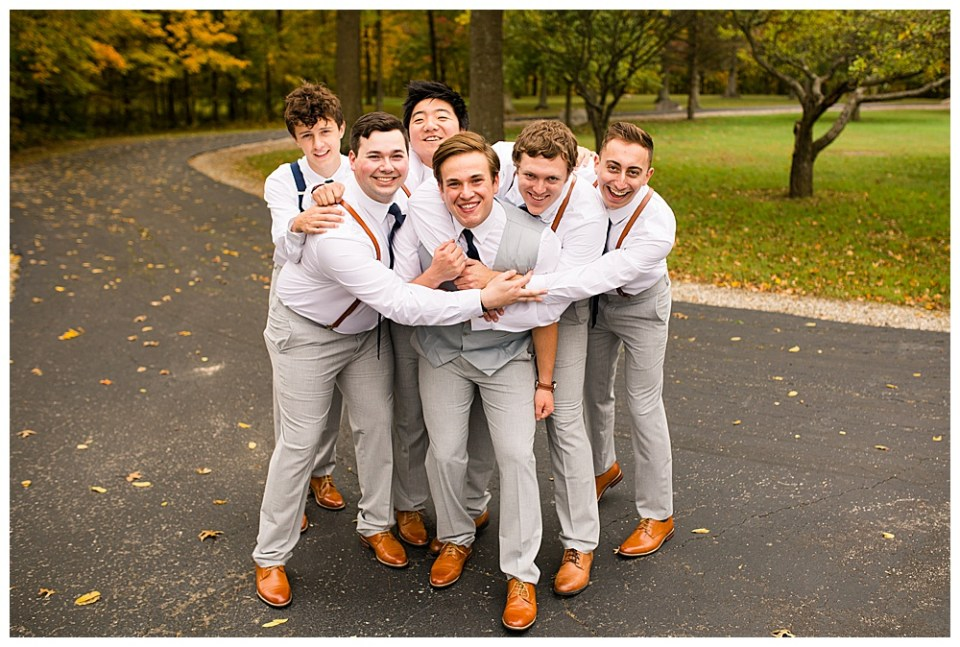 An image of the groom surrounded by his groomsmen as they join their arms around the groom, laughing and having fun together on the wedding day