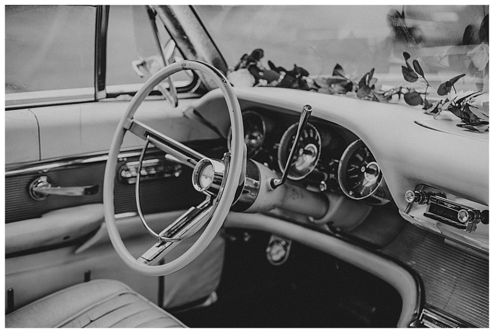 An image in black and white of the inside of a restored vintage car that the bridal couple will drive to begin their honeymoon