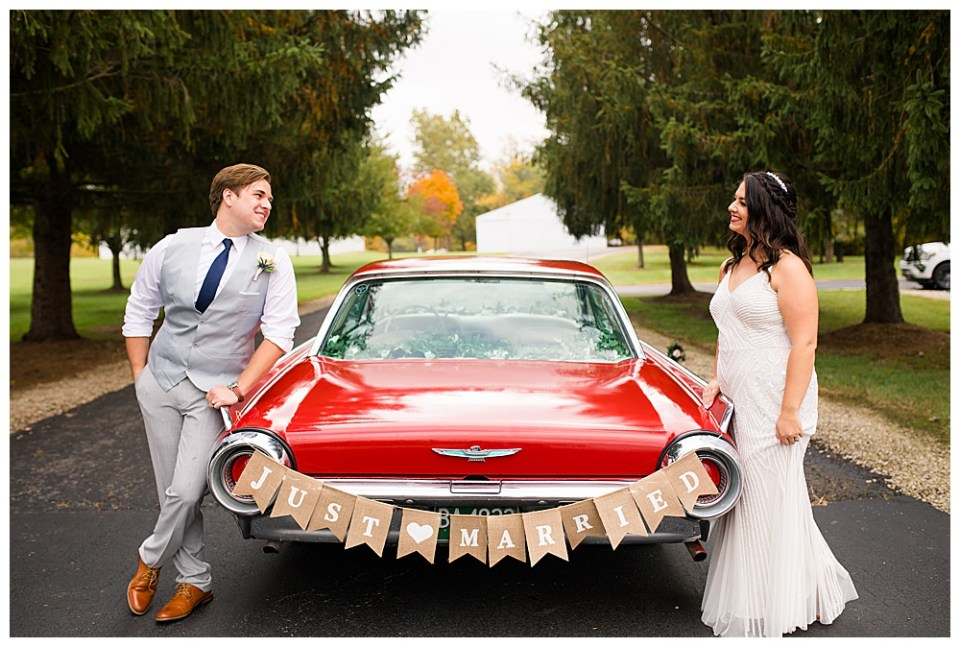 "A picture of the bride and groom leaning on each side of a restored vintage car with a ""Just Married"" sign, as the couple smile at each other, waiting to jump in the car to get away after the reception"
