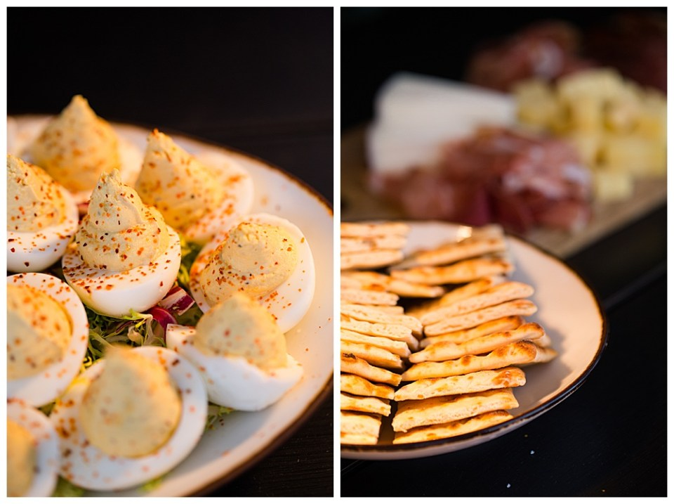 An image of a closeup view of delicious deviled eggs on a plate and a view of cheese and crackers on plates, waiting for guests to enjoy at the wedding reception