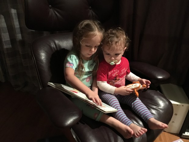 Sister reading to little bro before bedtime.