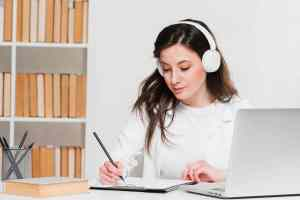 femme devant un ordinateur écrivant sur un bloc note