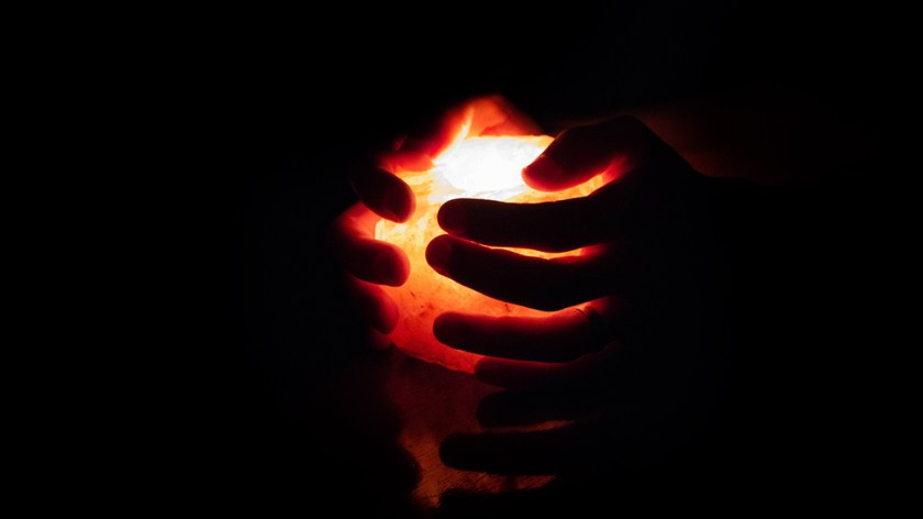 Hands holding a salt candle, which illuminates surrounding darkness
