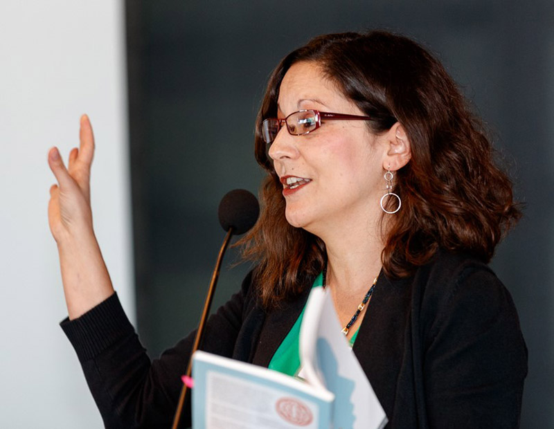 Woman holding book and speaking into mic with one hand expressively raised
