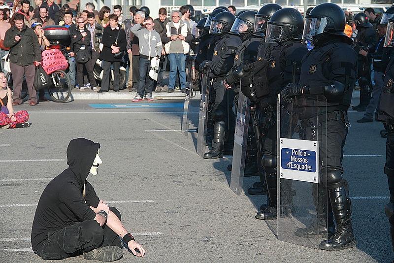 Protestante sentado frente a los Mossos d'Esquadra manifestándose por los recortes. Date 29 February 2012 Source https://www.flickr.com/photos/mierdadeartista/6942001877/in/photostream Author Arturo Puente