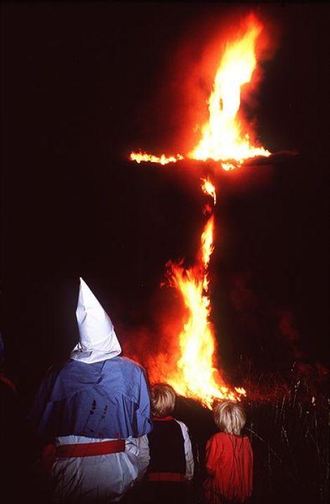 El miembro del Ku Klux Klan Joe Gosiniak observa cómo una cruz arde. Le acompañan sus hijos.  Autor: Paul M. Walsh, 1987. Fuente: Wikimedia Commons (CC BY-SA-3.0.)