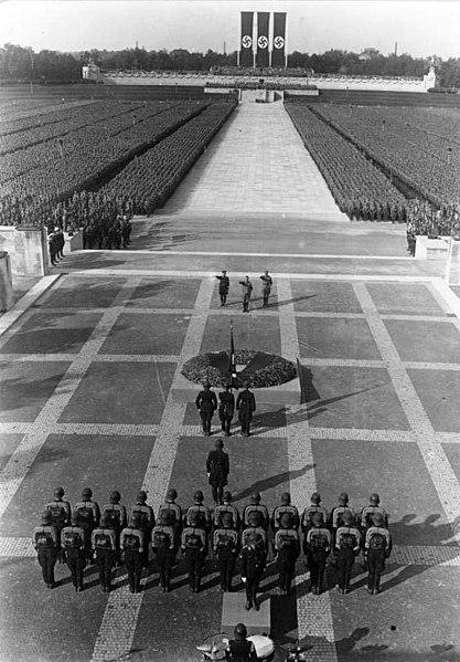 Heinrich Himmler, Hitler y Viktor Lutze realizan el saludo nazi en el Congreso de Nuremberg en Alemania. Autor: Georg Pahl, 1934. Fuente: Bundersarchive, Bild 102-04062A  (CC-BY-SA-3.0-DE.)
