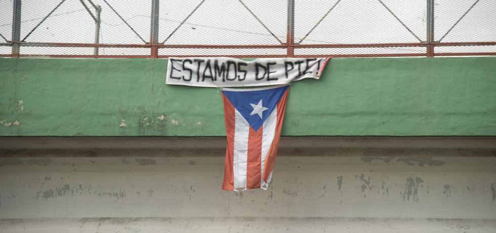 """A flag hangs from a highway overpass that reads """"Estamos de pie,"""" in Caguas, Puerto Rico, Oct. 2, 2017. """"Estamos de pie"""" translates to """"We are standing,"""" which is meant to motivate people to stay strong and overcome the disaster left behind Hurricane Maria. (U.S. Air Force photo by Airman 1st Class Caleb Nunez)"""