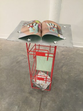 "Bookstand, (collaborative), soft cover books, plaster with enamel, pigment, and marker, enamel and acrylic on panel, found stand, 34"" x 9.5"" x 11"", 2016."