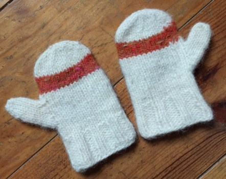 A picture of some child's mittens in cream wool with an orange stripe across the palm