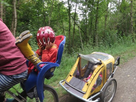 A child with her face covered in a cycling helmet sits in a bike seat resting her feet on her mother's back. Another child is in a yellow child trailer behind.