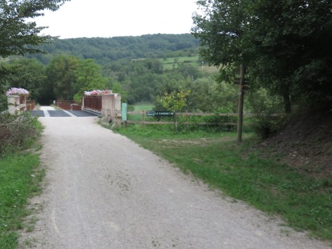 A stony track leading to a bridge with flower baskets along the top, green fields and woodland in the background