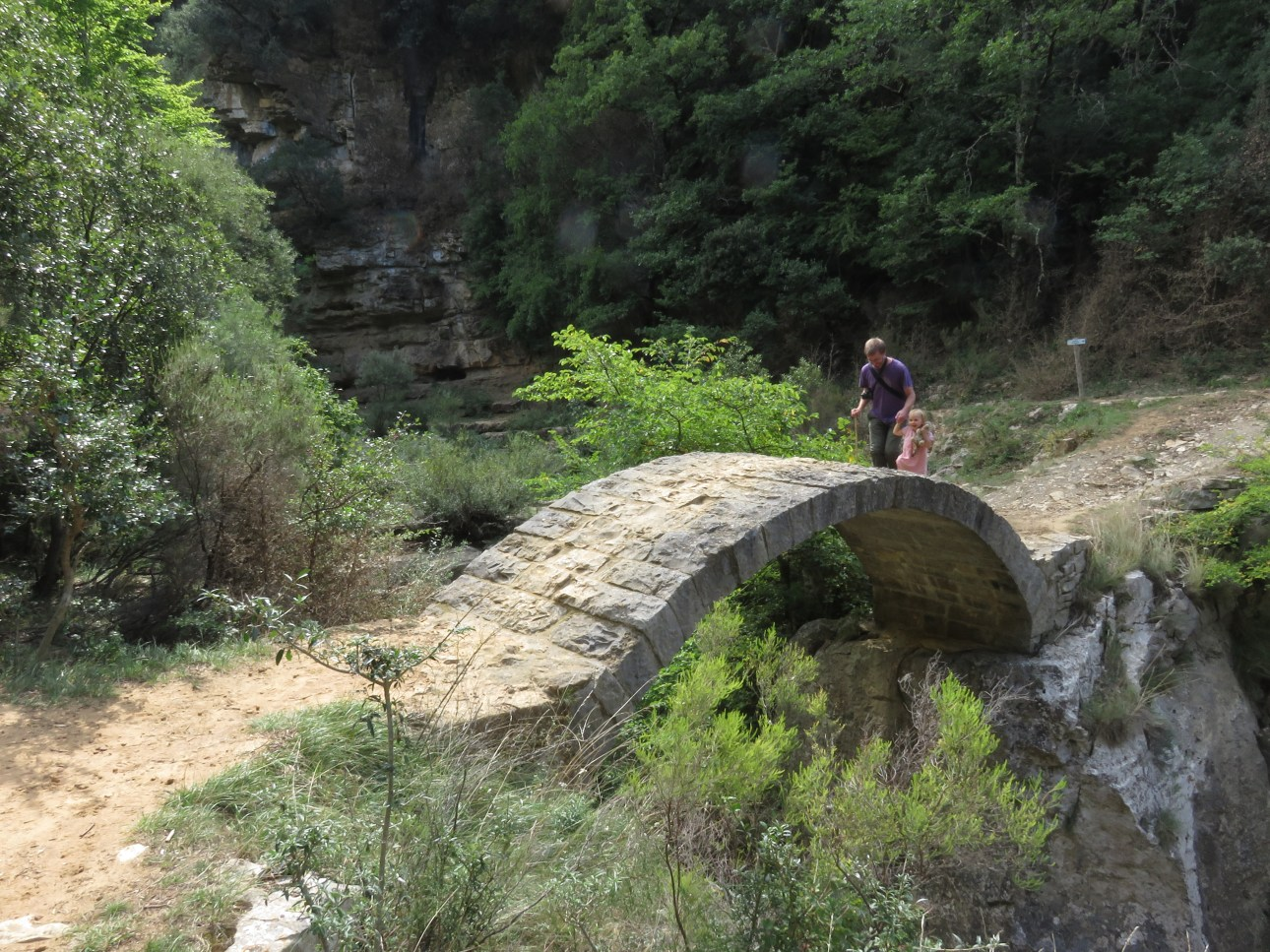 A small child in a pink dress holds a mans hand and crosses a small stone bridge over a ravine