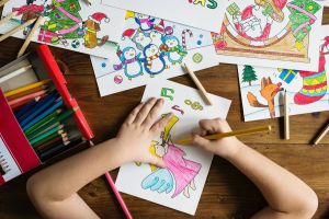 A view from above, looking down on a child's hands holding a yellow pencil and coloring in christmas scenes.