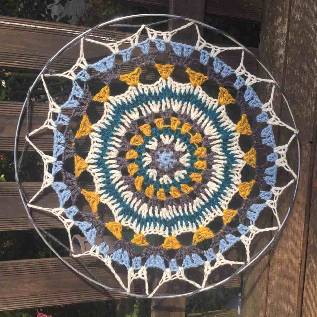 A mandala made of white, blue, grey, peacock blue, and yellow yarn and fixed within a metal hoop to make a circle.