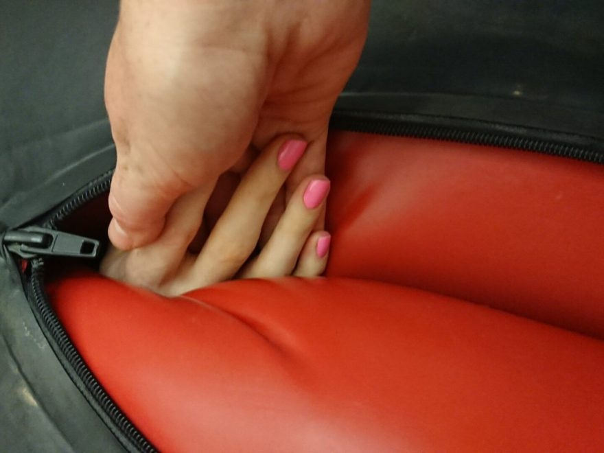 One hand with manicured pink nails reaching out from inside an inflated latex body bag to hold the hand reaching down.