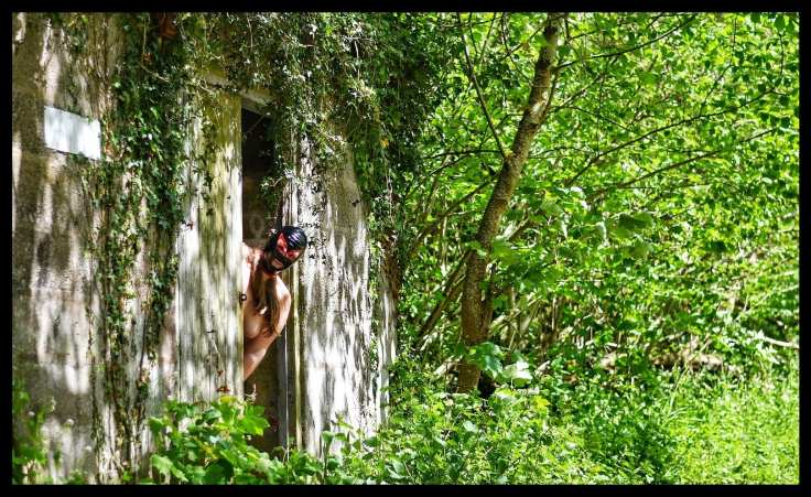 A derelict train station building in the middle of a leafy green scene. Peeking sinfully out of the doorway is a naked lady wearing a black latex hood with red trim around her eyes.
