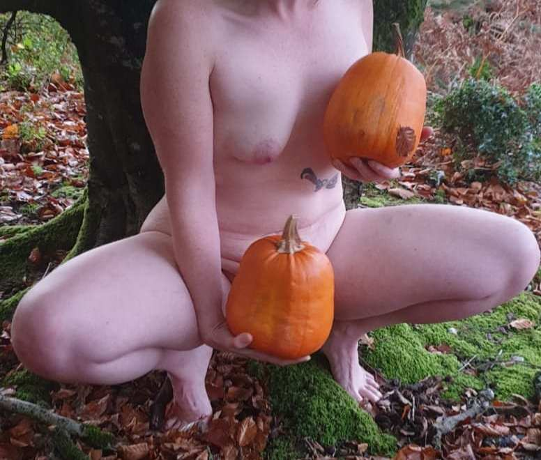 Naked lady with pumpkins in front of a tree for halloween