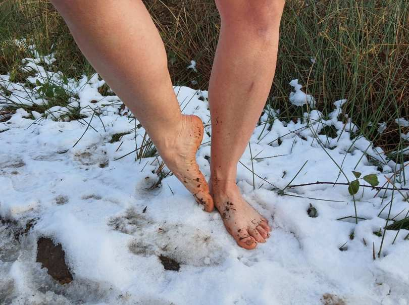 Naked legs and feet standing barefoot in the snow