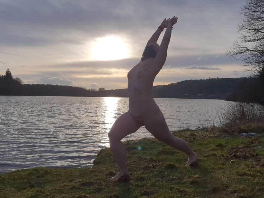 Naked lady doing outdoor yoga: Lakeside warrior pose