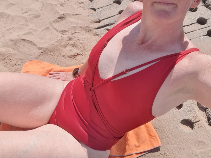 Life lesson #10: rember to celebrate header image. Lady in a red swimming costume, fresh from the sea with water drops on her skin