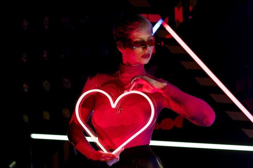 Easter Bunnies header image shows a woman holding a neon heart to her chest.