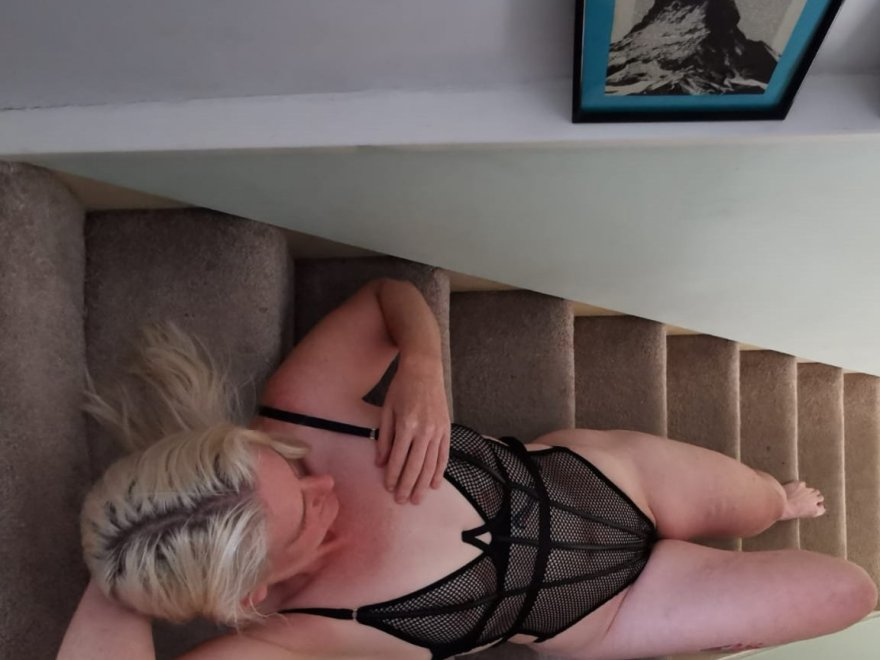 Halfway up the stairs header shows blonde woman in black fishnet lingerie body laying back on her staircase.