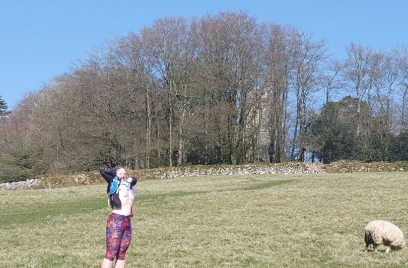 Stepping back in time header shows a female runner pulling her top up to expose her breasts in the middle of a field. A church is visible through the still naked trees, and a sheep strolls by.