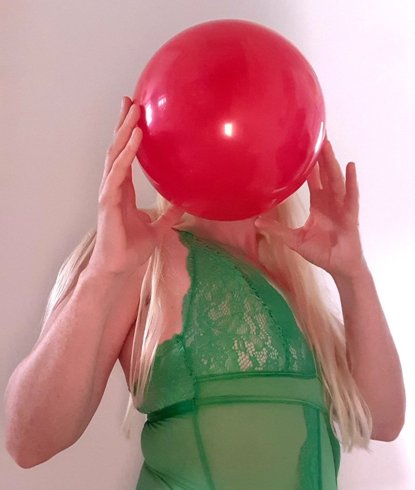 L is for Looner header shows woman with long blonde hair in green lingerie blowing up a red balloon.