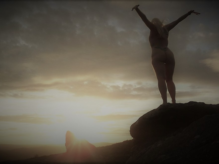 Changing nature of explorations shows naked lady standing on a rock facing away from the camera watching the sunset and reaching up and out with her arms.