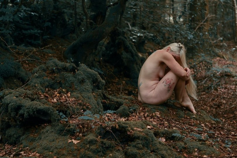 a life without regrets header shows blonde lady sitting on the woodland floor, curled over her legs with head buried into her knees, and blonde hair falling over arms and legs.
